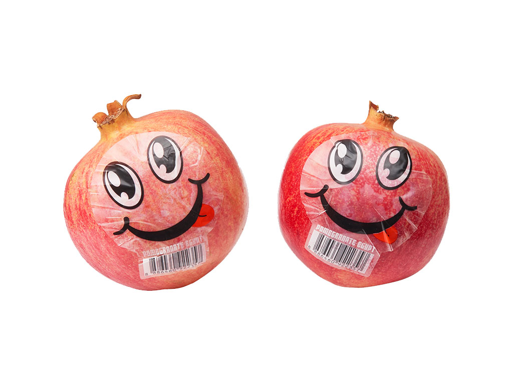 Two Egypt pomegranates with a smiling face sticker