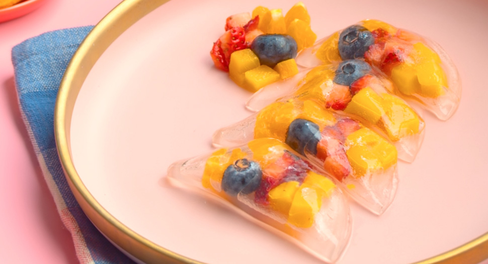 Diced fruits wrapped in transparent dumpling skin on a pink and gold-rimmed plate