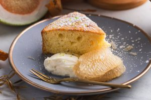 a slice of pomelo cake dusted with icing sugar and served with fresh pomelo and whipped cream