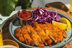 Crispy fried chicken schnitzel served with a side of salad and curry ketchap